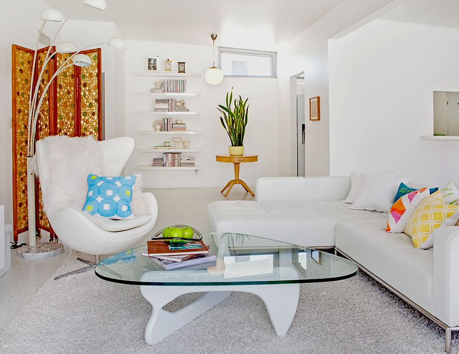 white on white living room with a arc floor lamp, womb chair and sectional sofa. Colorful pink, ornage and green throw pillows provide all the color in the room.