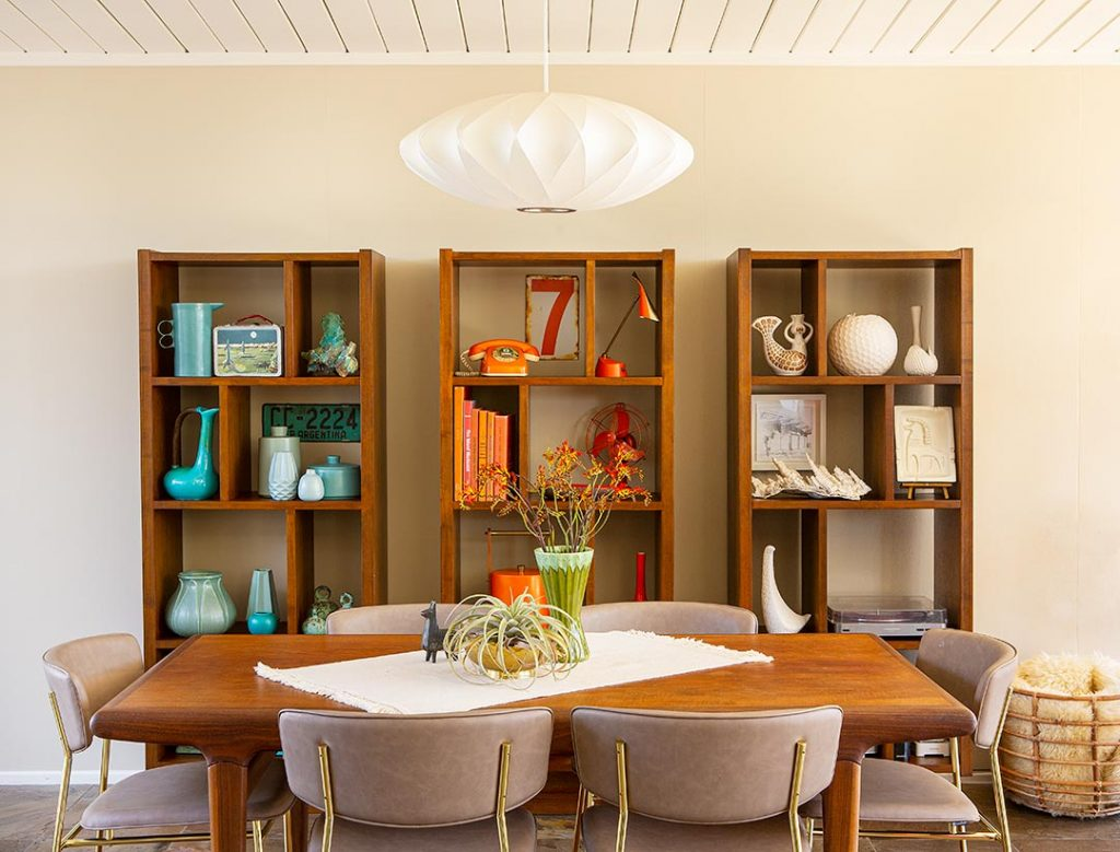 an eichler dining room with three modular bookcases all in a row, each decorated with single color collectibles.