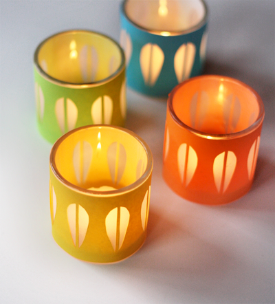 Four candle holders in green, yellow, orange and blue