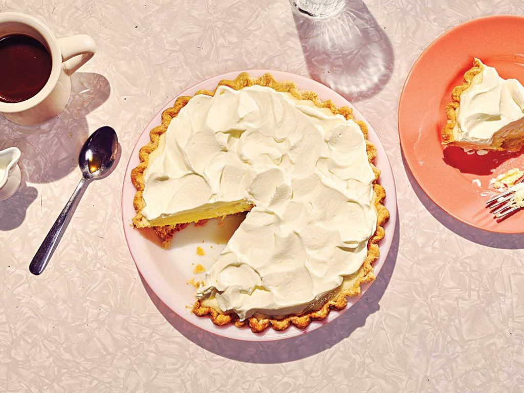 Overhead photo of lemon chiffon pie with slice on a plate