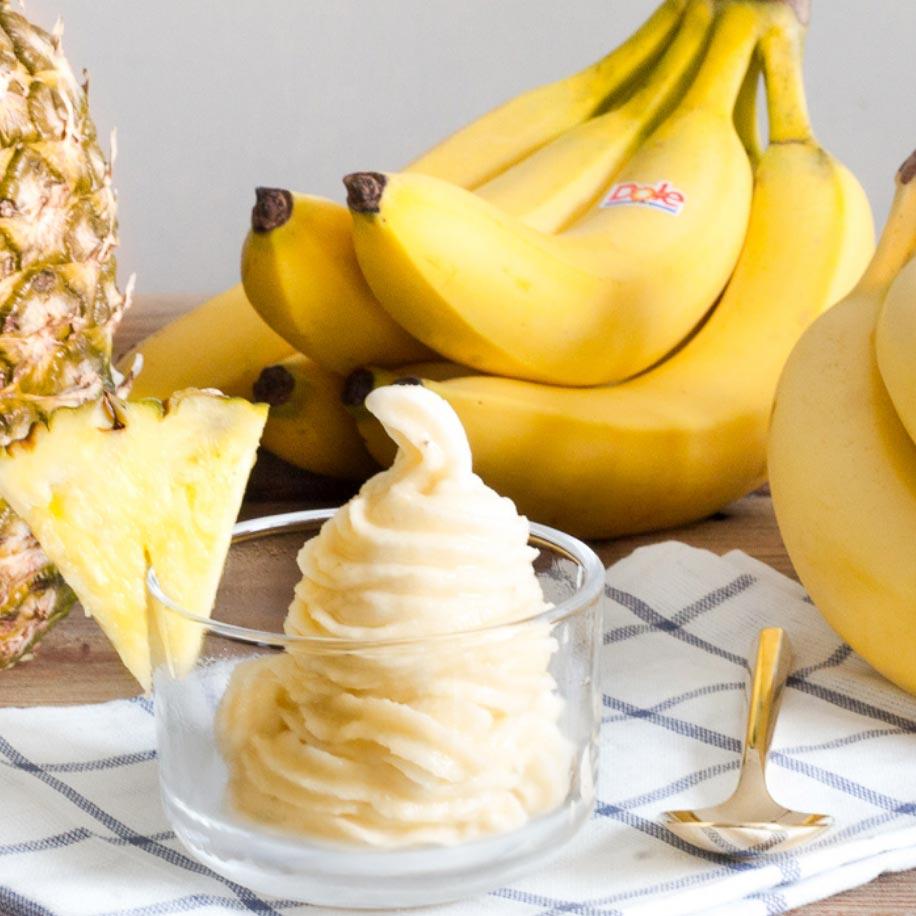 a Dole whip soft serve dessert in a glass bowl surrounded by it's ingredients: pineapple and banana