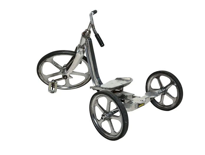 A child's silver tricycle with black handles and wheels.