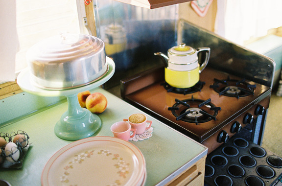 Vintage trailer with an antique stove and jadeite pie stand