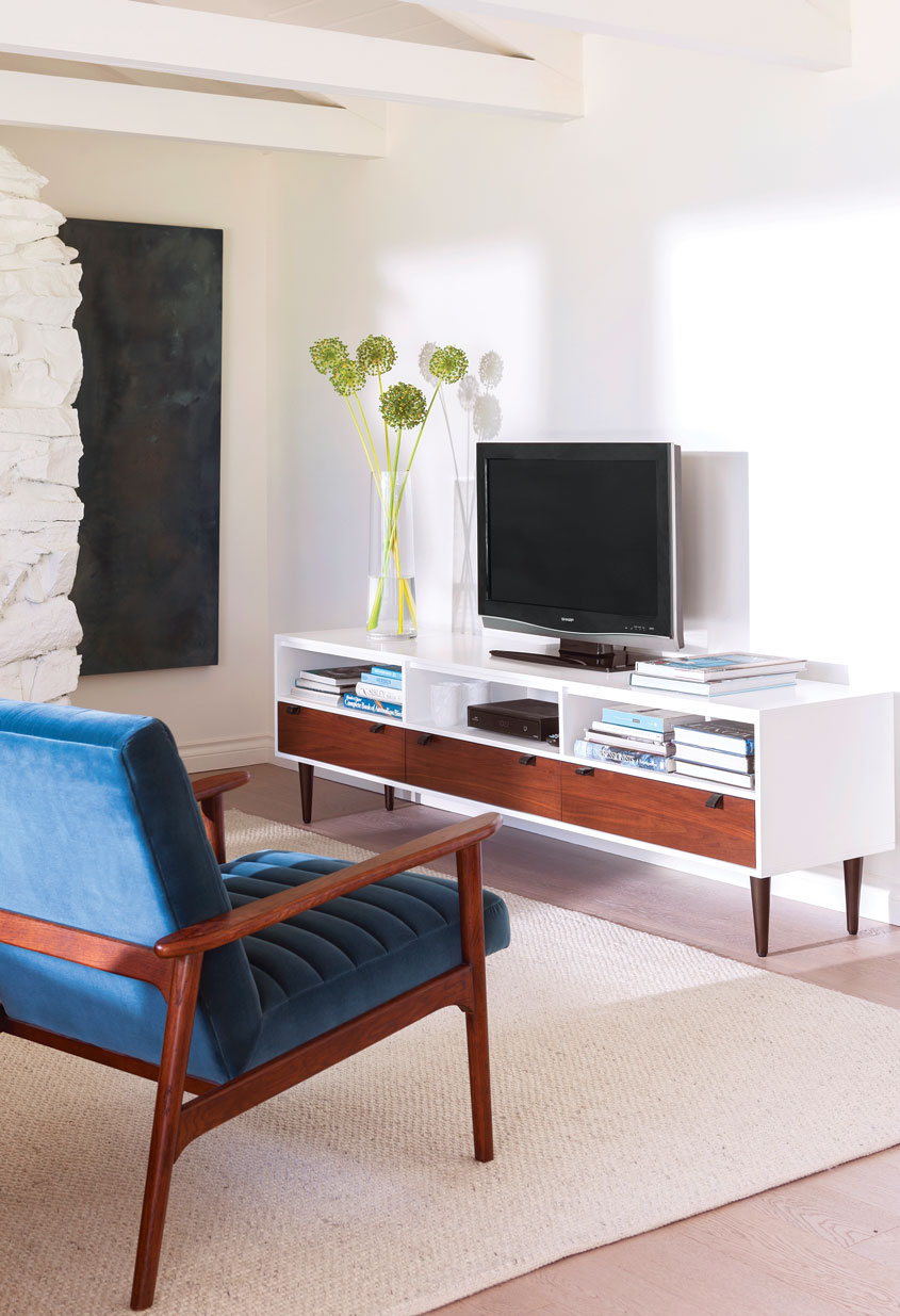 a living room with a low entertainment console with walnut drawers against a white wall