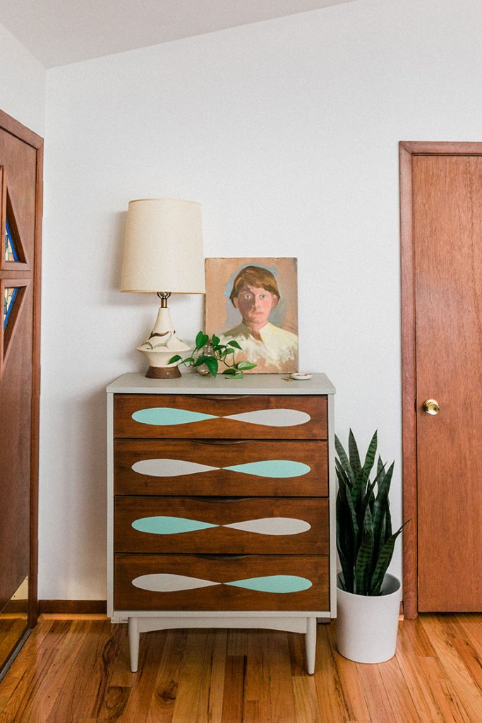 a midcentury dresser with teardrop-shaped designs painted on the drawers