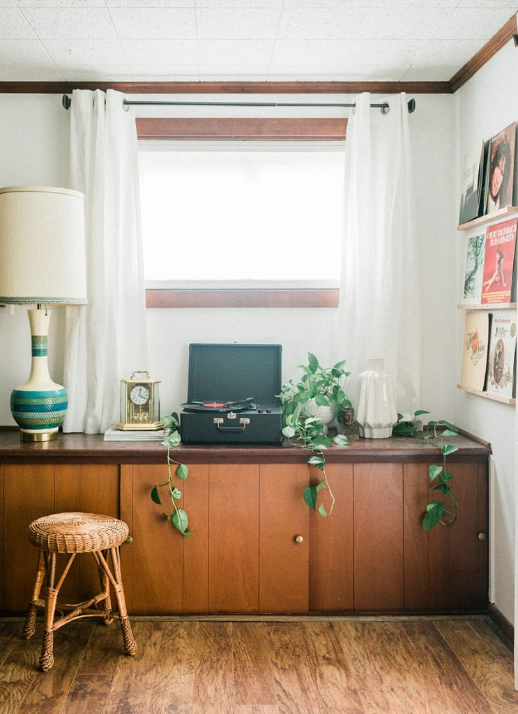 built in credenza in a mid century modern house with ivy pants draping over the edge, a tall vintage lamp and album covers on the wall as art