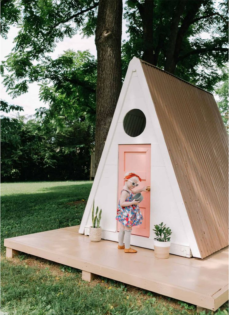 A white A-frame playhouse with a pink door sits on a wooden platform. A little girl wears a colorful dress as she pulls the doorknob.