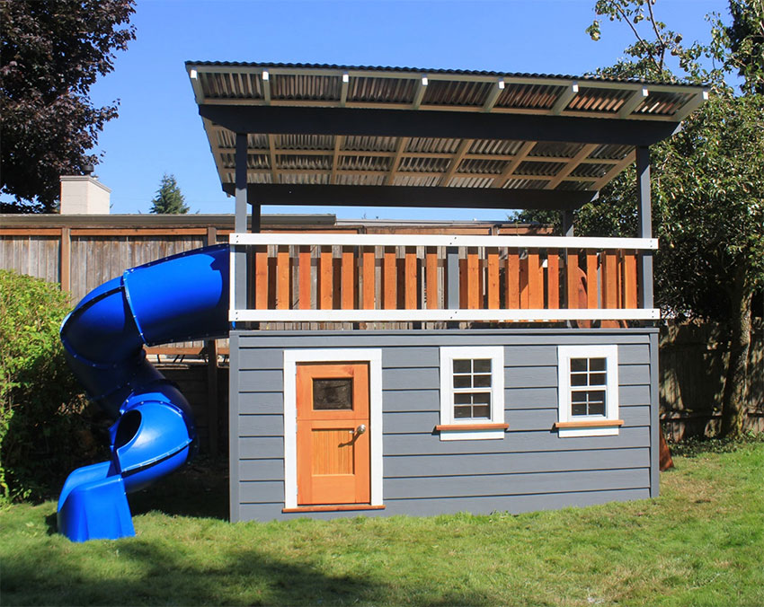 A child's playhouse with grey siding and wooden door has an overhang for shade and a blue twisted slide coming from the upper level