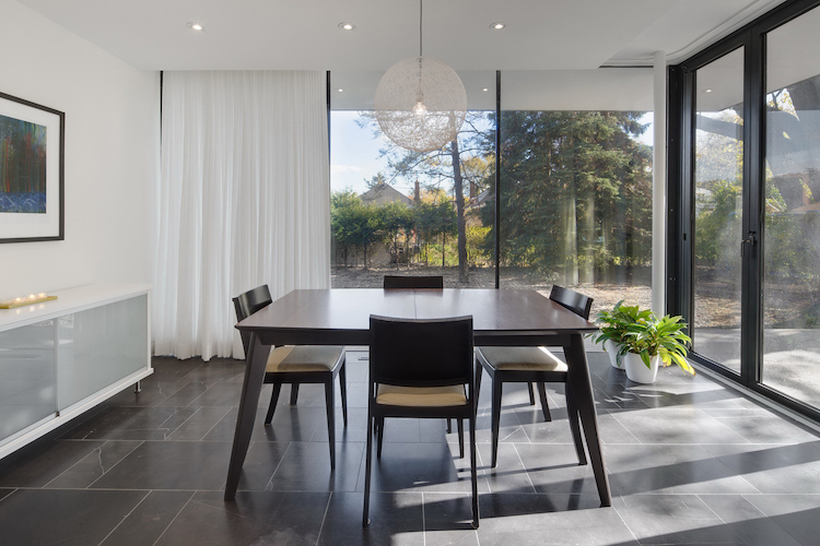 modernist dining room with glass wall panels and dining table