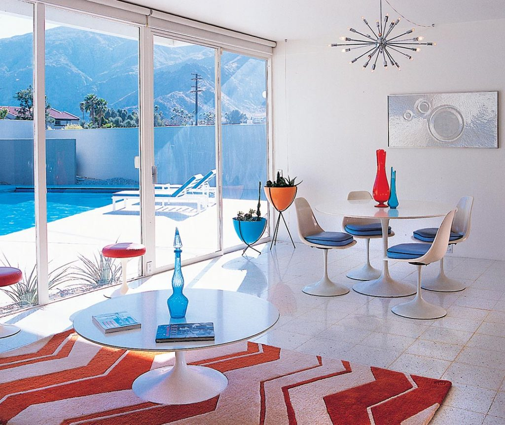 a midcentury modern dining room in a Wexler home in Palm Springs. White terrazo floors gleam and mirro the white Saarinen tupil table and chairs dining set. A chrome sputnik light hangs above.