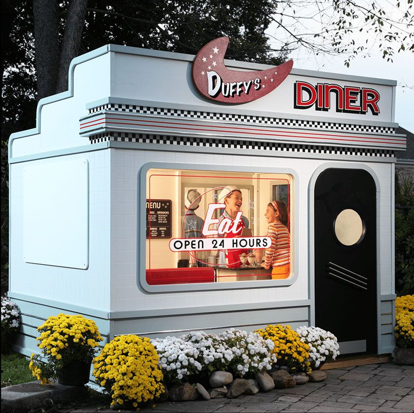 A child's sized 1950s diner with a black door and black-and-white checkered trim detail. Children can be seen laughing through the window.