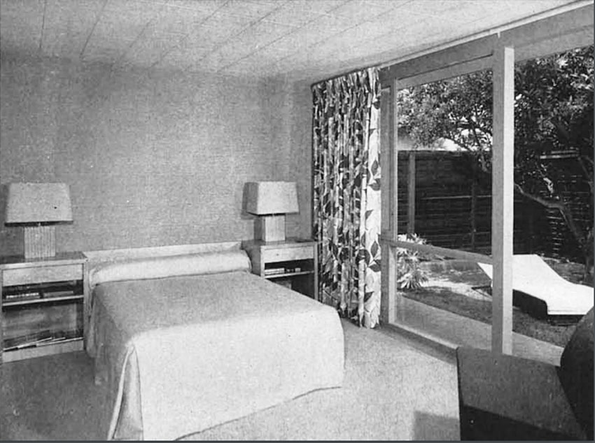 Black-and-white daytime photo showing a bed and two side tables with large windows to the right and floral curtains