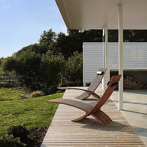 wooden slat cantilever patio loungers on a sleek minimalist patio overlooking green grass