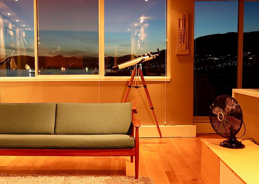 a twilight view out of the window of a modern condo in vancouver with a mid century sofa