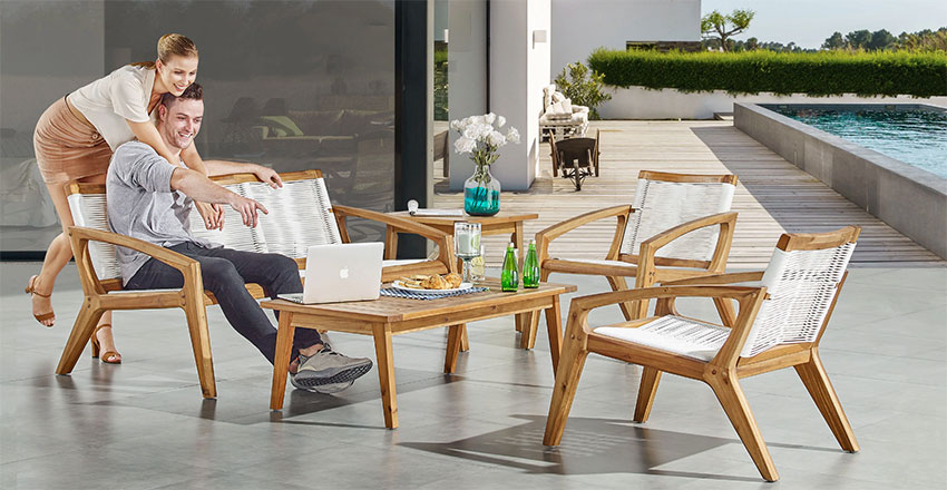 teak mid century style patio furniture set with two arm chairs, one sofa and a matching coffee table set in a modern backyard with raised pool