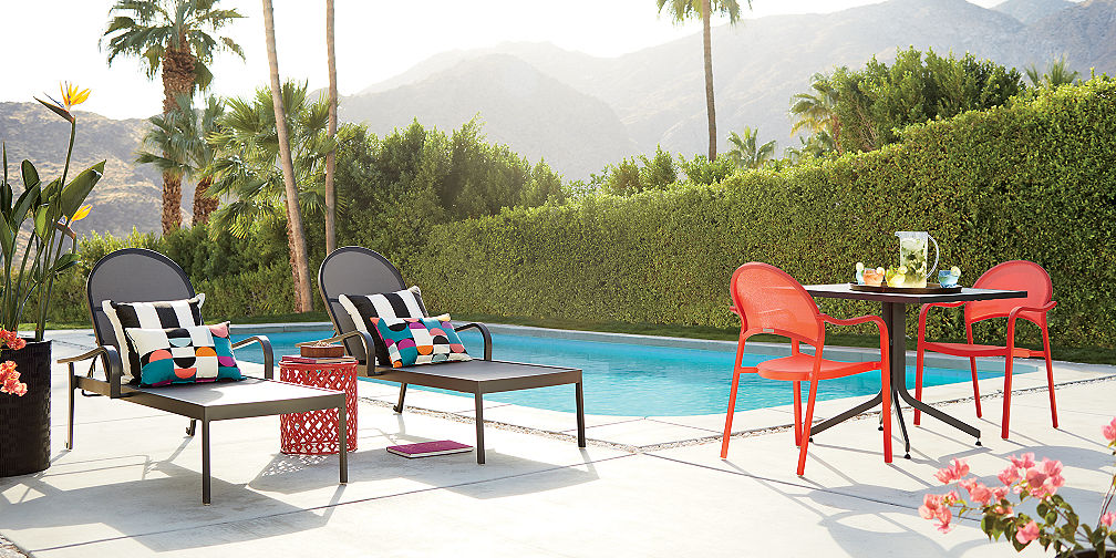 lanai modern patio furniture collection of black chaise lounges and red bistro chairs sites poolside in a modern garden