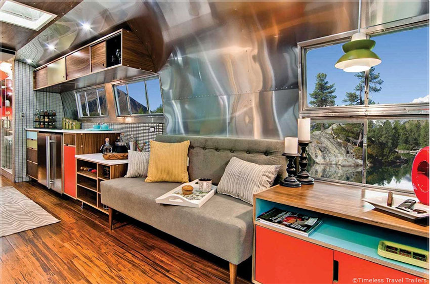 Vintage trailer with grey mid century style sofas and colorful Kerf style built in cabinet storage.