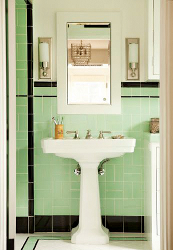 A bathroom sink against mint green mid century modern bathroom tile with black accents along the bottom, top and corner.