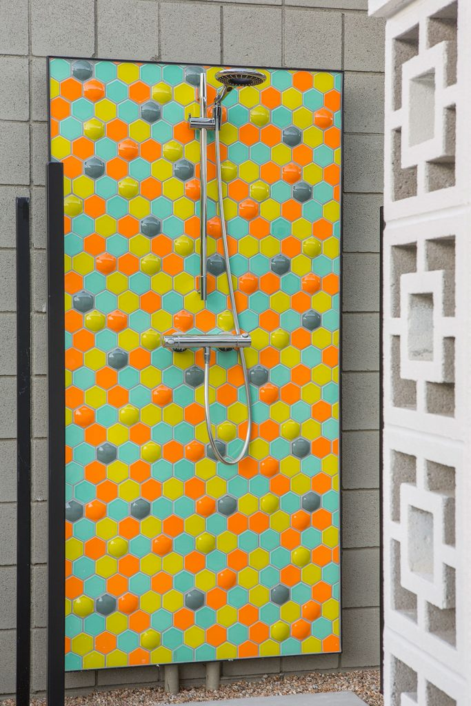 An outdoor shower has a wall created with dimensional hexagon tiles in different bright colors