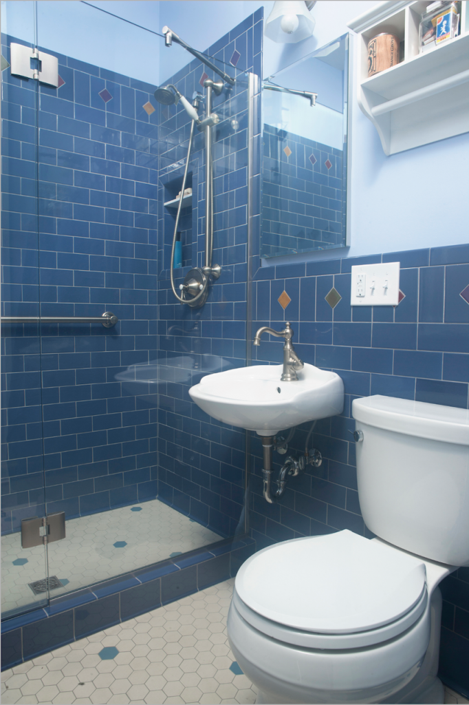 Blue subway tiles are on the walls of the bathroom while the floor is mainly white hexagon tiles with some blue accent mid century modern bathroom tile