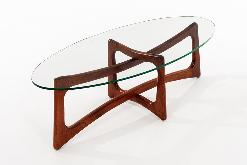 An Adrian Pearsall coffee table with an oval glass top and wooden legs.