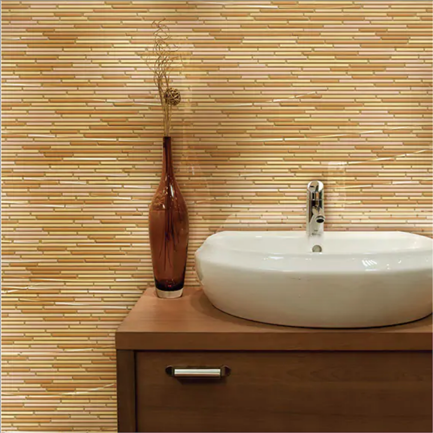 Thin linear glass mid century modern bathroom tile in varying shades of cream and tan are laid in a somewhat-organic pattern in this bathroom wall