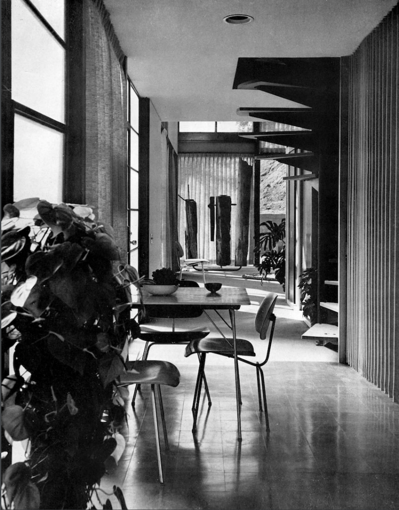 : A black and white photograph with a dining table and chairs in the foreground to the left and a spiral staircase further back to the right. A living space is seen in the back