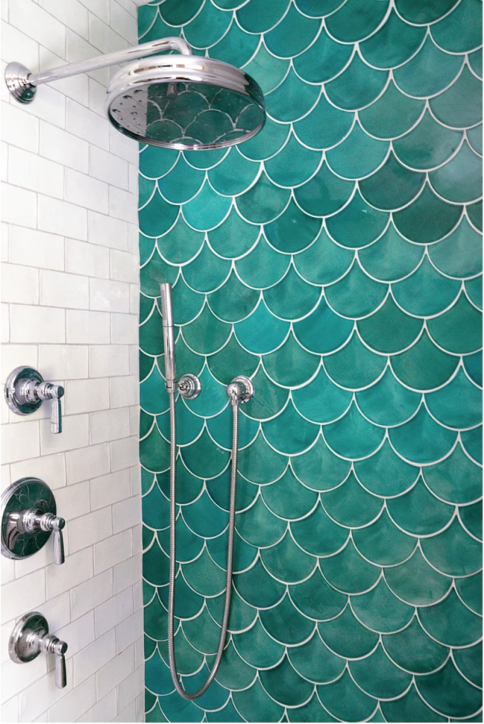: Emerald green tilesmid in the shape of fish scales pair with white subway tiles in a shower.