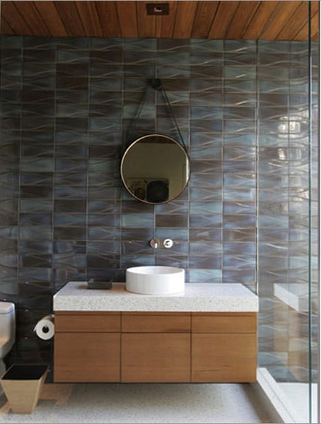 A bathroom has a floating vanity and back wall of textured dimensional mid century modern bathroom tile in varying shades of blue.>