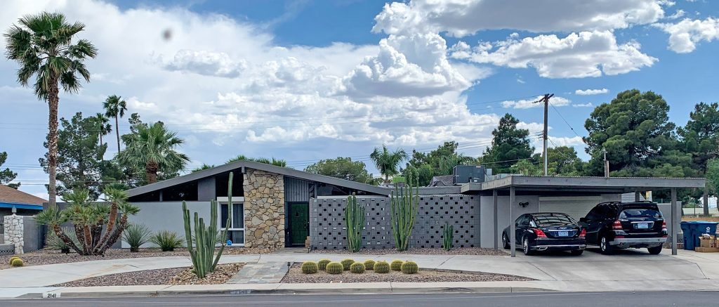 Grey toned mid century modern ranch style home with green cactus landscaping, a carport and breeze blocks