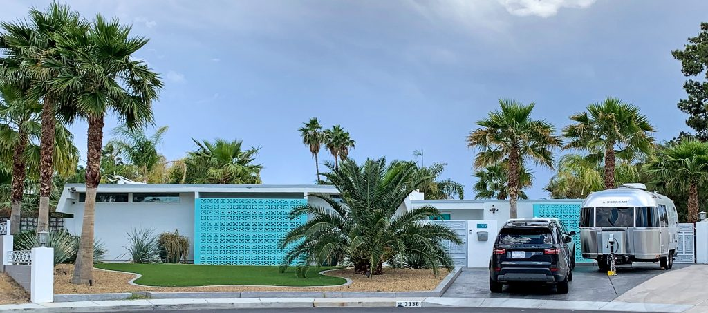 Grey mid century modern ranch style home in Paradise Palms with turquoise breeze blocks and airstream parked in driveway.