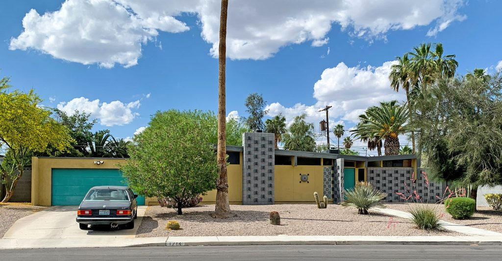 Yellow mid century modern ranch style home in Paradise Palms with grey breeze blocks and turquoise garage and front door.