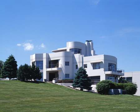 A large home with curved sides and balconies that are almost nautical. The house is perched on a green hillside and the sky is bright blue