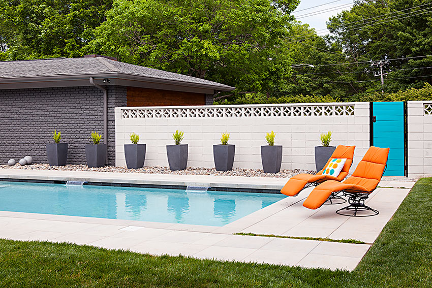 a modern rectangular pool with orange lounge chairs and breeze block fencing behind