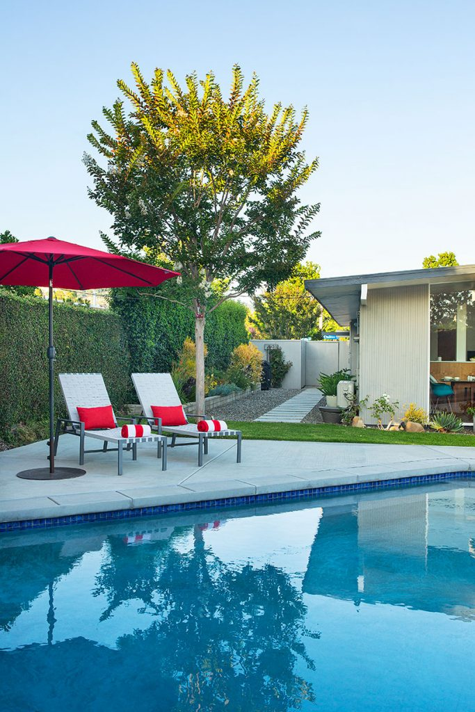 modern pool with a simple modern lounge chair and red umbrella next to it.