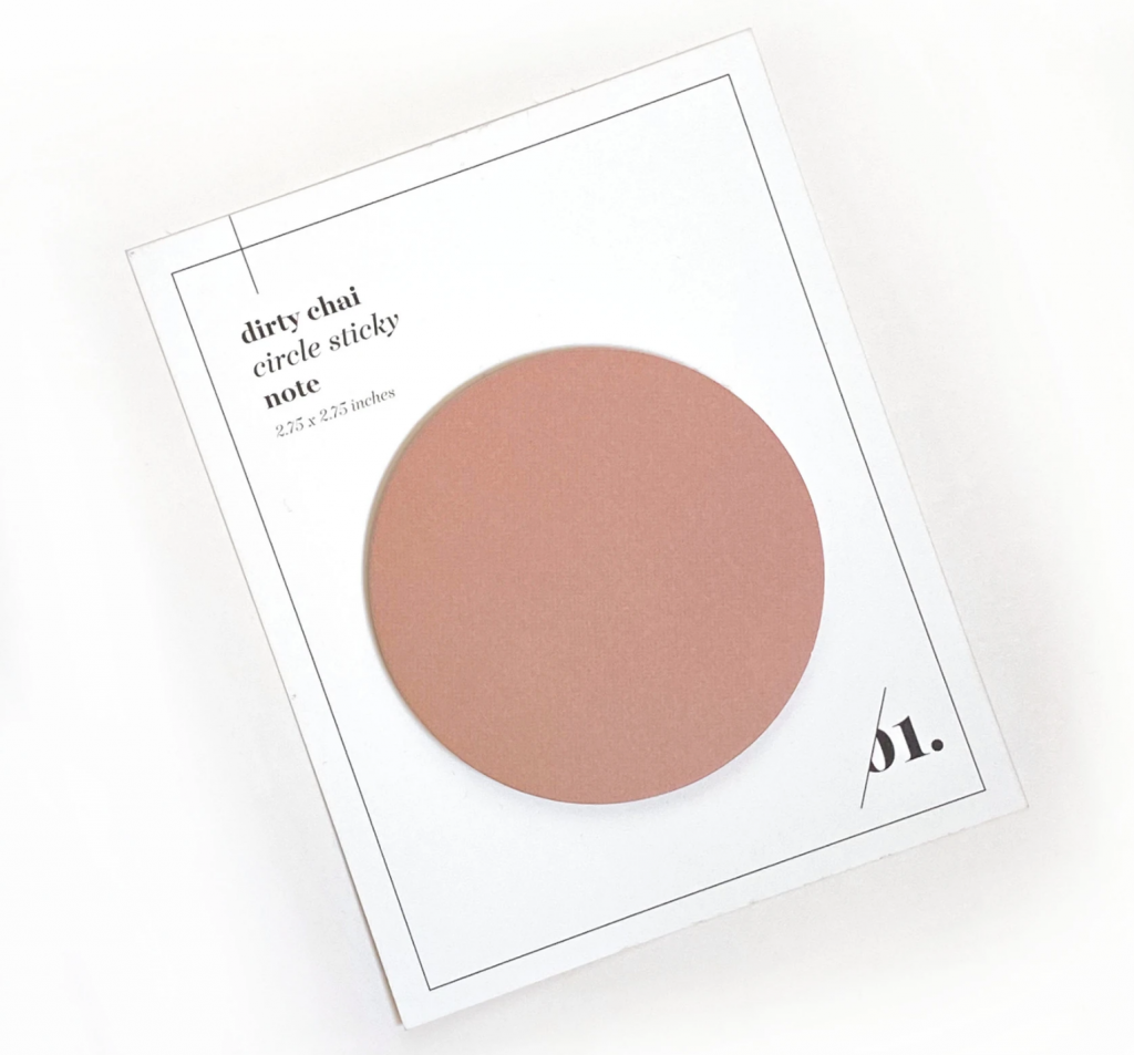 A chai-colored circular sticky pad sits on a white card backing