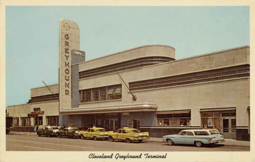 Color postcard from the 1940s showing a Greyhound bus station built with curved lines and several horizontal tiers. There are 5 taxis lined up in front of the structure.