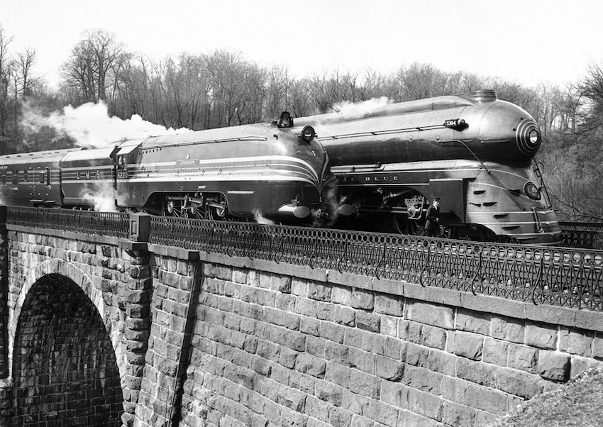 A black and white photo of two trains traveling parallel on a bridge circa 1939. The trains are very sleek and streamlined