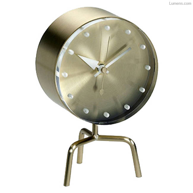 A small retro brass clock with a circular face and white dot markers for the time. Three small brass legs support the clock