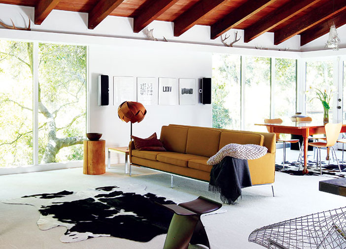 a mustard Paul McCobb couch in a mid century living room with exposed beams