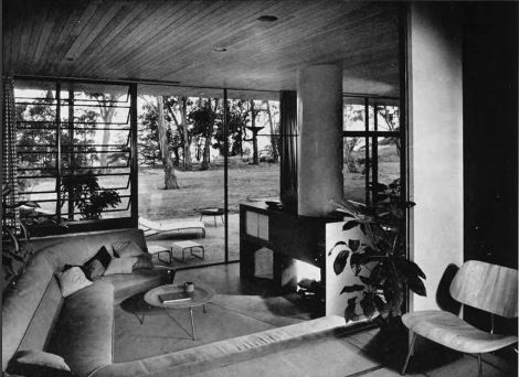 A black and white photo of inside the Case Study House #9 of a curved built-in couch and floor-to-ceiling windows in the background