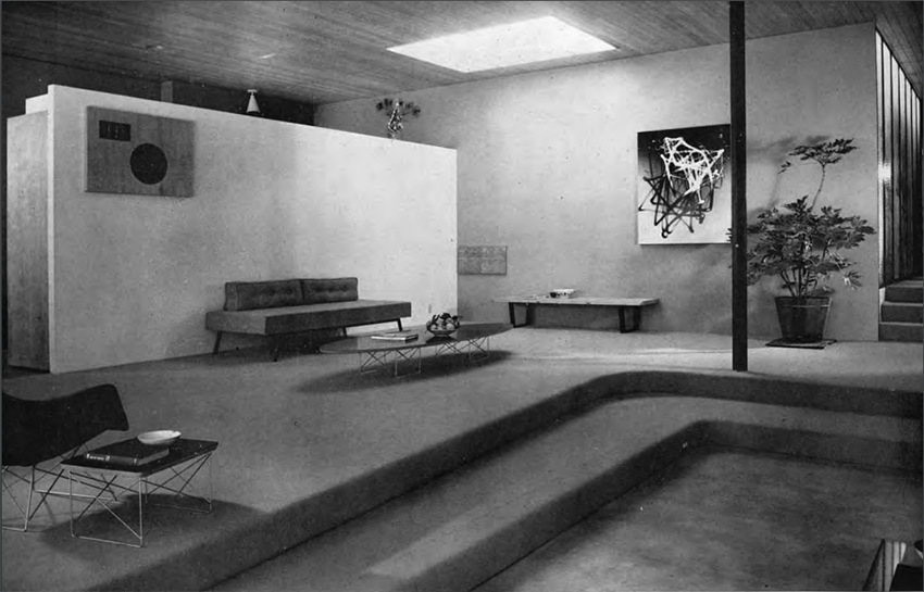 A black and white photo of a living room with a small couch, coffee table and a sunken in portion of the room in the foreground.>