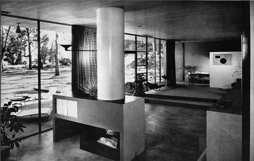 : A black and white photo showing a rectangular fireplace in the middle of a large living room