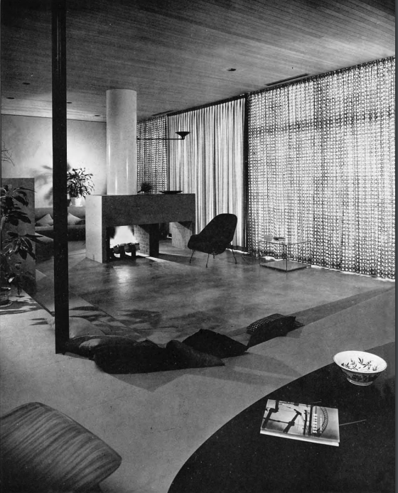 A black and white photo of a sunken-in living room with a large rectangular fireplace in the center and windows shut with draperies on the right