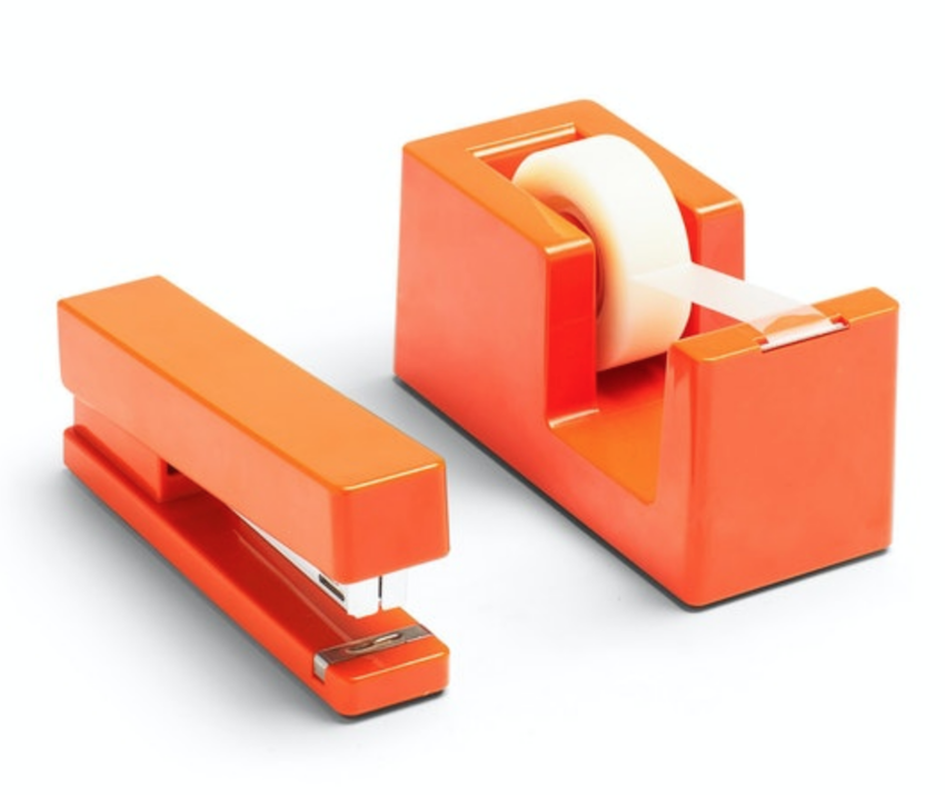 mid mod office supplies: An orange retro stapler and tape dispenser sit next to each other
