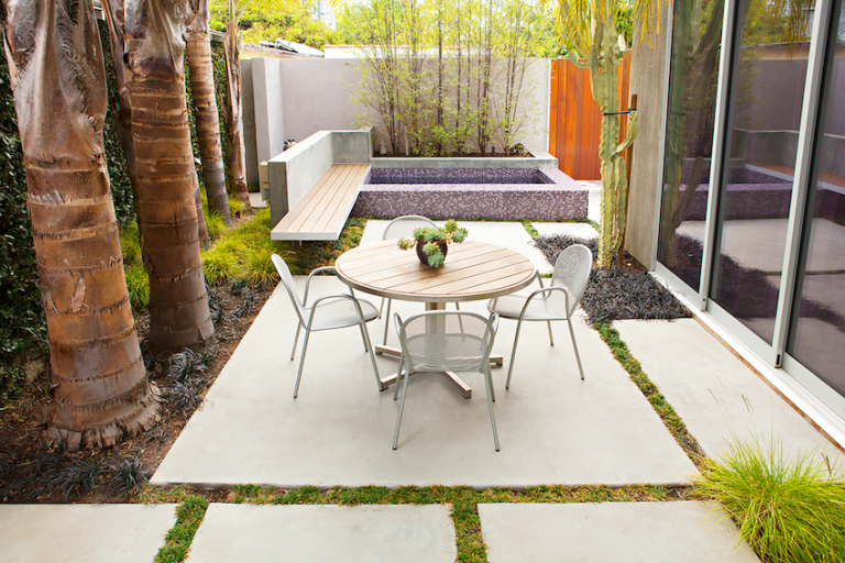 An image of a backyard area with a tiled spa and floating bench are in the background and a table with 4 chairs in the foreground