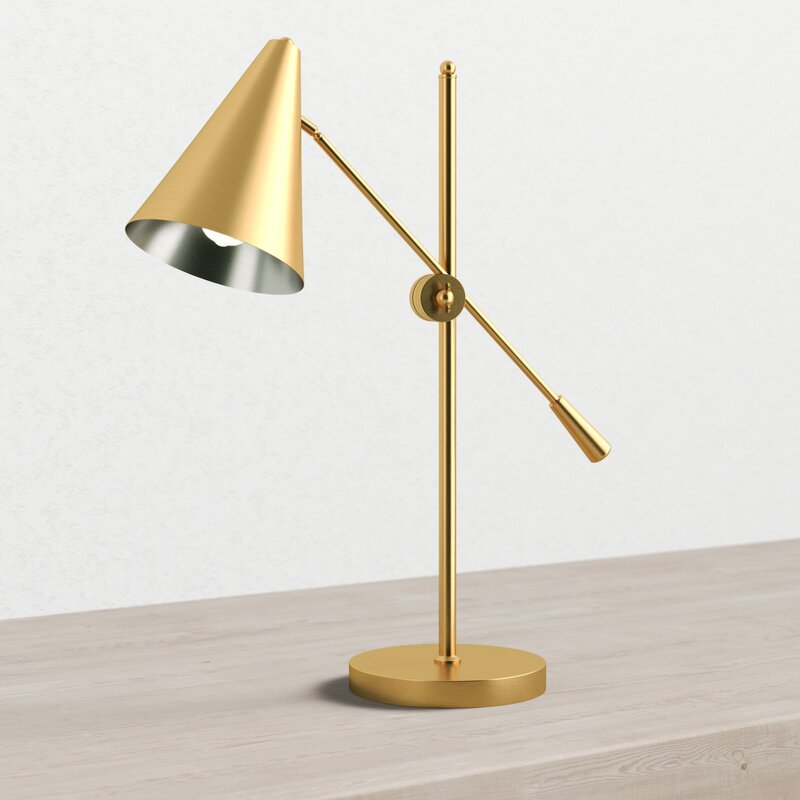 A gold lamp with a conical head sits on top of a desk
