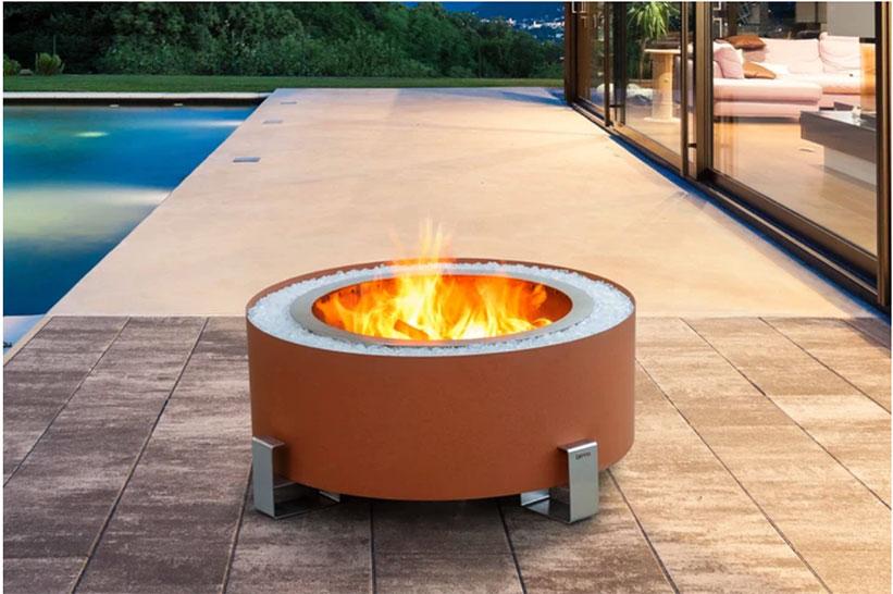 a modern fire pit near a pool