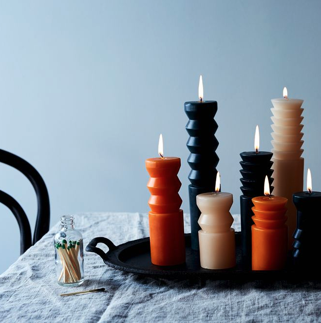 collection of multi-colored candles with various shapes lit on a table