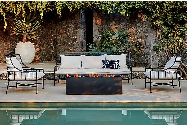 long rectangular fire pit in the middle of a seating area in front of a pool